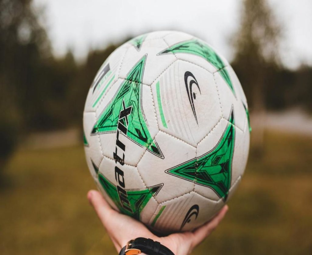 A close shot of man holding football in his hand