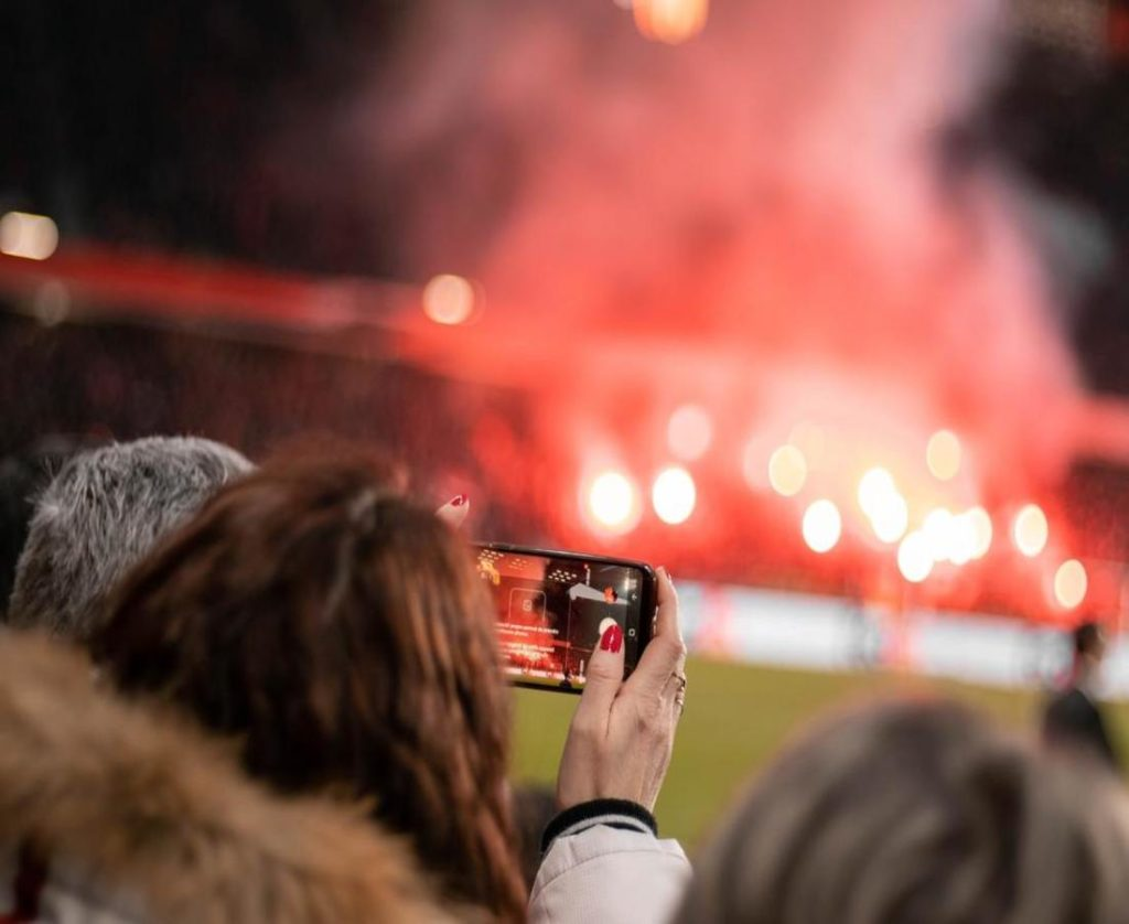 An amazing background bokeh photograph of a girl making football match video with her mobile in hand