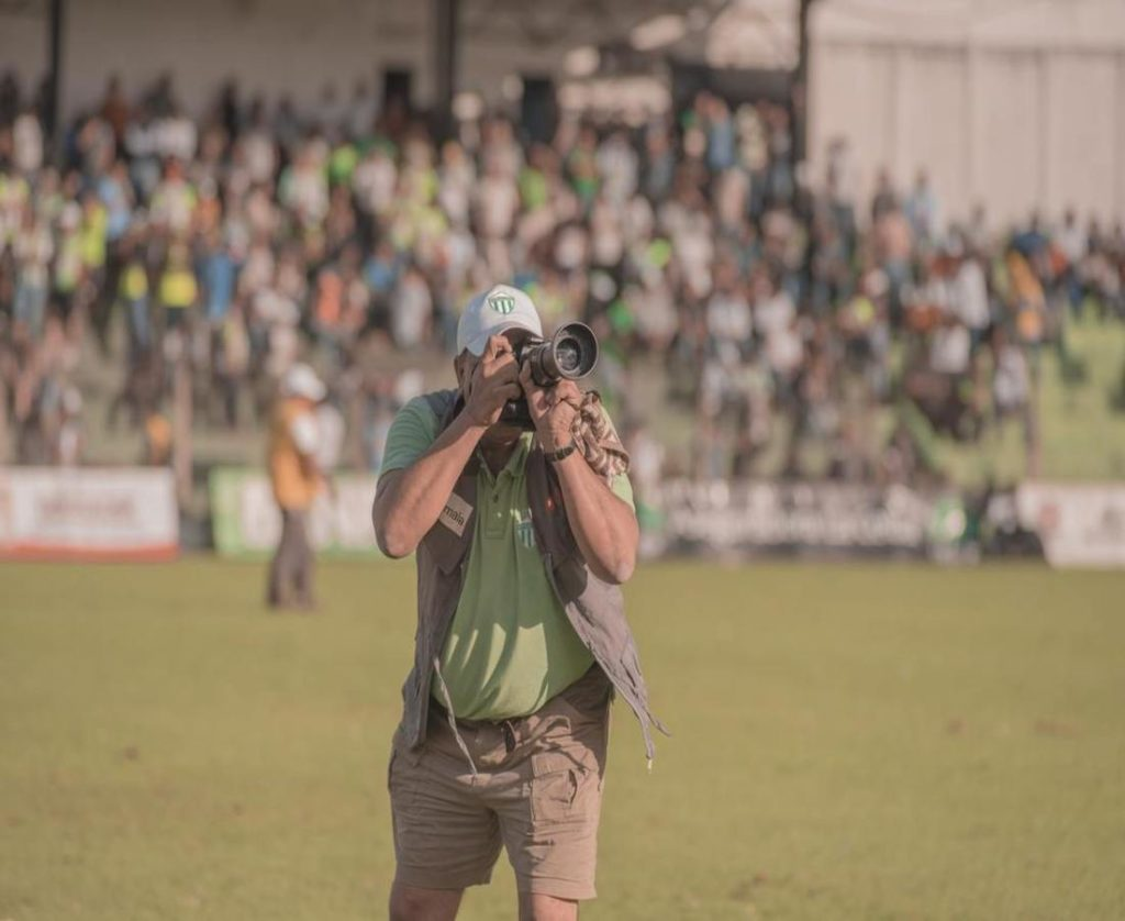 A man capturing the photos with best camera lens in a sports ground