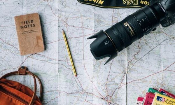 best Nikon Lens for Photography with a pencil, bag, and book on decorated table