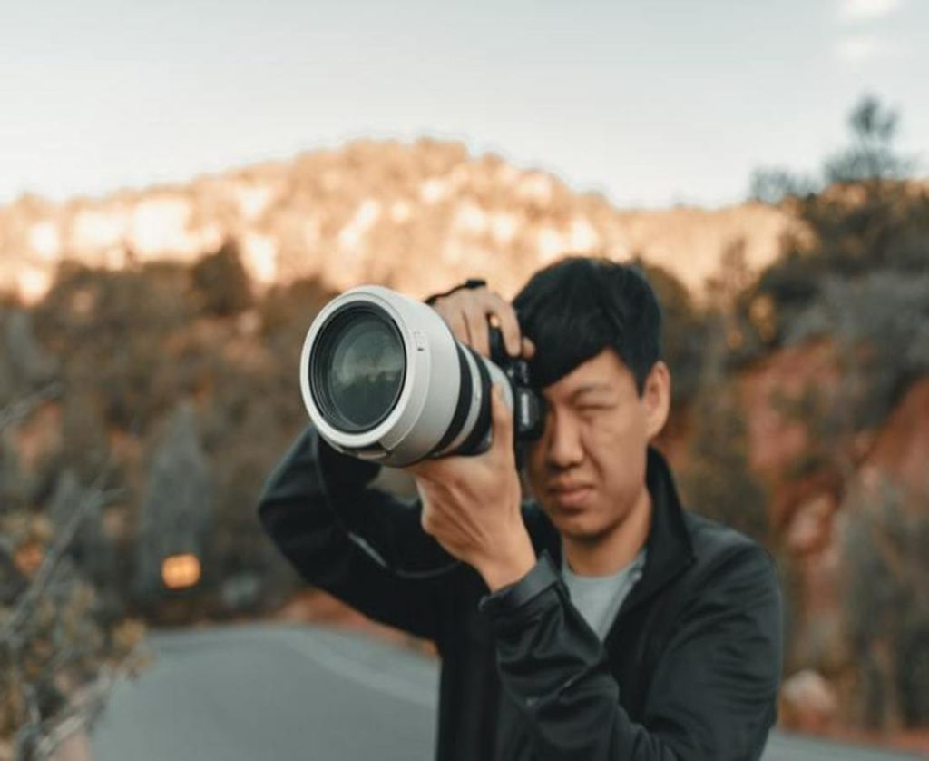A man is capturing the portraits Best Canon Lens for Portraits and Wedding Photography