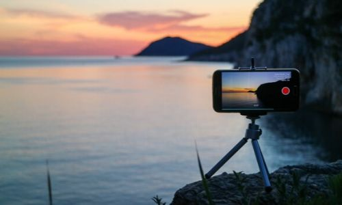 A mobile phone on a tripod recording the timelapse and telling How to Start Vlogging With Phone