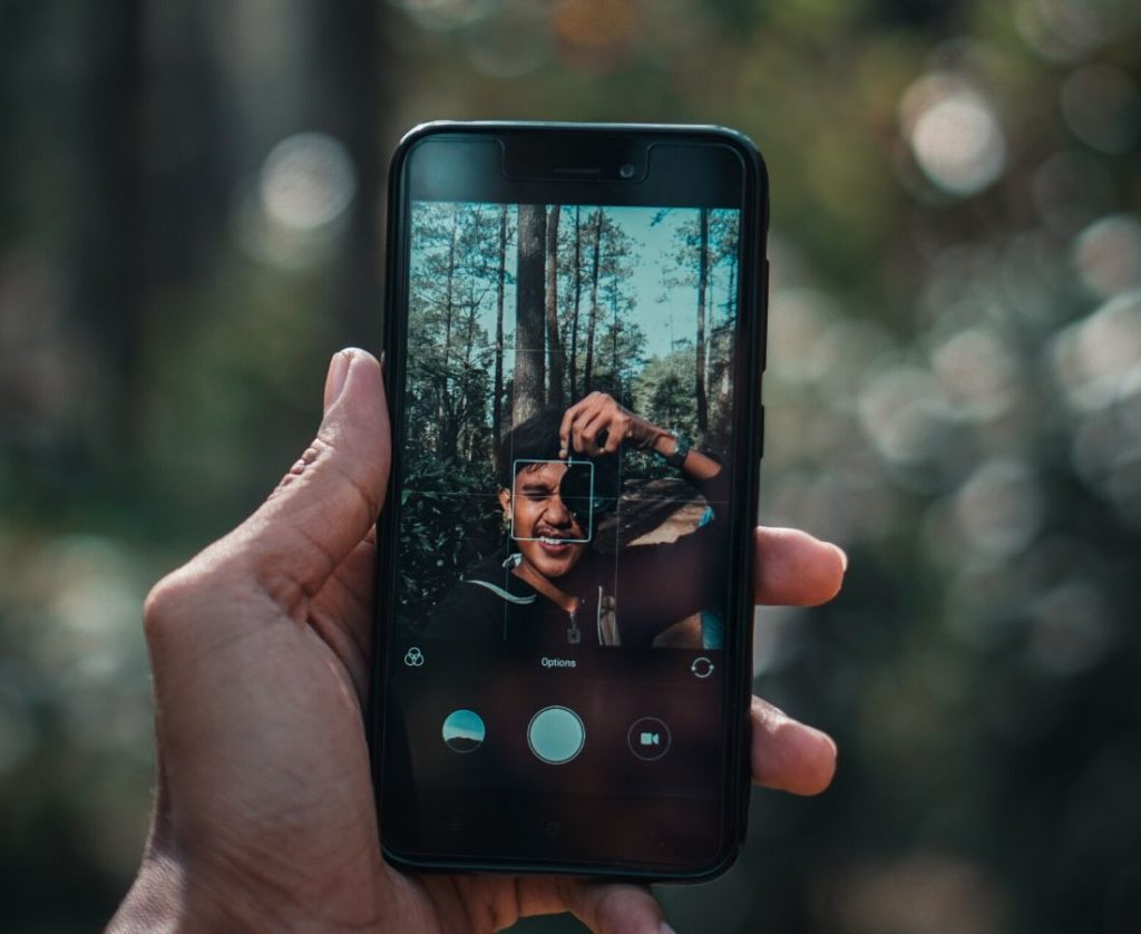 A man making vlog with his phone in a forest