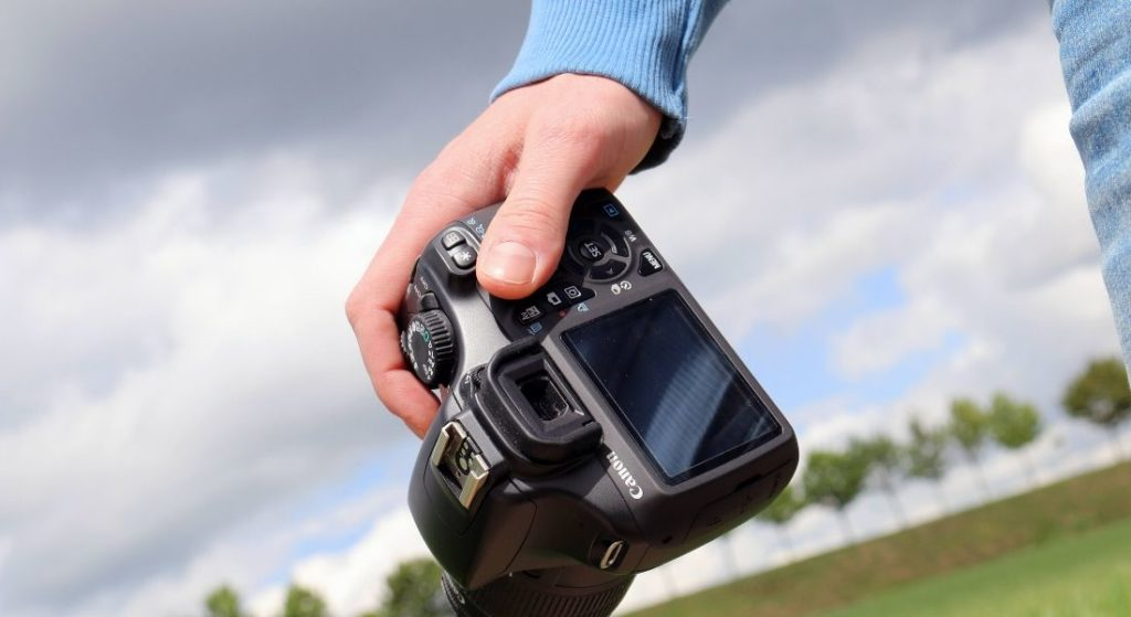 A man holding the DSLR Camera in hand